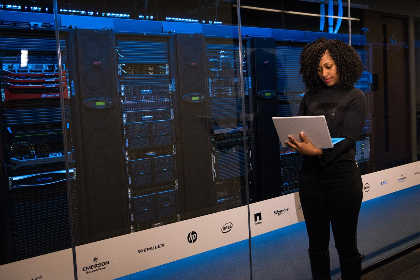 A woman holding a laptop inside a server room